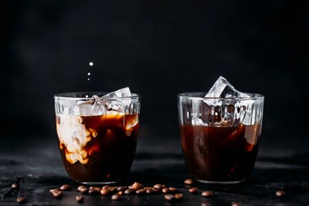 Coffee with ice in a glass, milk poured into a glass.