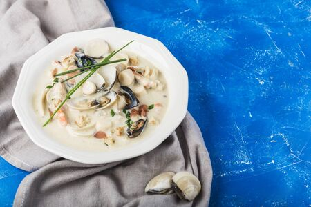 Clam chowder in a white plate. The main ingredients are shellfish, broth, butter, potatoes and onions. New England soup also known as Boston clam chowder. On a light classic blue background. Side view. Copyspace.