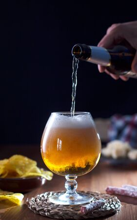 Man pouring craft beer into glass, dark wooden 写真素材