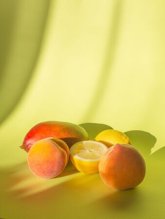 Fresh fruits on a pastel green background with shadows, vertical orientation