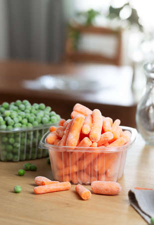 Frozen vegetables such as baby carrot and peas in the storage boxes on the kitchen table. Freezing is a safe method to increase the shelf life of nutritious foods