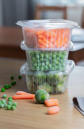 Frozen vegetables green peas in the storage box on the kitchen table, vertical orientation. Freezing is a safe method to increase the shelf life of nutritious foods Stockfoto