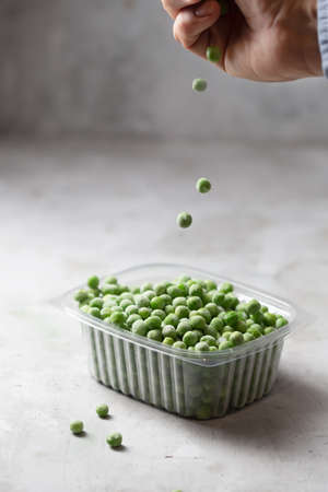 Frozen vegetable green peas in the storage box on the kitchen table, vertical orientation. Freezing is a safe method to increase the shelf life of nutritious foods Stockfoto