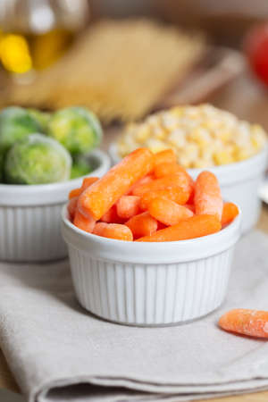 Frozen vegetables such as baby carrot and Brussels sprouts in the bowls on the kitchen table. Freezing is a safe method to increase the shelf life of nutritious foods Stockfoto