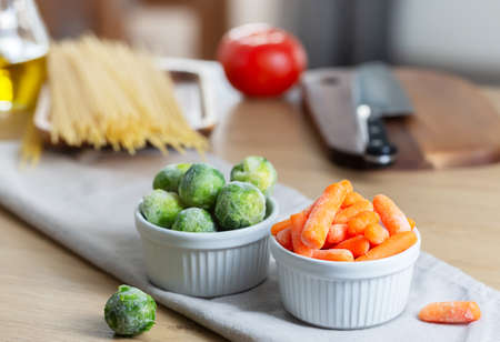 Frozen vegetables such as baby carrot and Brussels sprouts as well as dry pasta on the kitchen table. Freezing is a safe method to increase the shelf life of nutritious foods