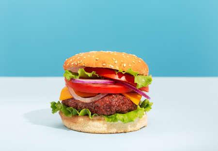 Fresh juicy beef hamburger placed on creative blue background