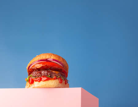 Fresh juicy beef hamburger placed on the pink stand and blue background. Copy space for text, trendy hero view, horizontal Stock Photo