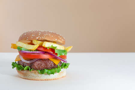 Fresh juicy beef hamburger placed on creative beige background with copy space