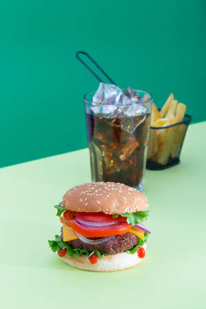 Fresh juicy beef hamburger placed on creative green background with potatoes and drink, isometric vertical orientation