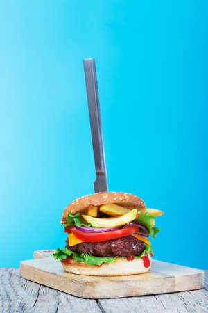 Fresh juicy beef hamburger with stuck knife placed on creative blue background