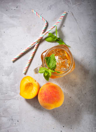 Peach ice tea on concrete gray background with mint and ice