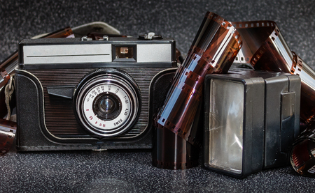 An old camera, flash and film tape