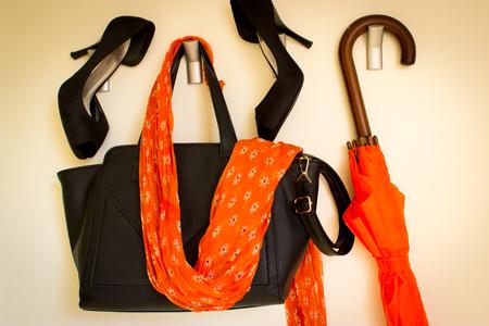 Black high heels and bag and orange sash and umbrella
