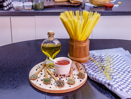 Uncooked spaghetti in wooden pot and spices on wooden plate on a kitchen table Stock Photo