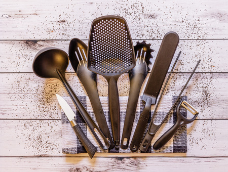 Various black kitchen utensils on white wooden background, top view Stock Photo