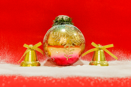 Colorful christmas ball  between two golden bells covered with snow on a red background, close up Stock Photo