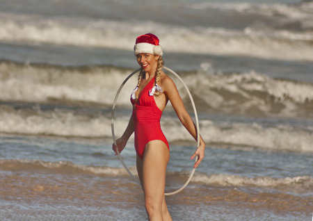 Girl in red and in Christmas hat with hula hoop on the beach