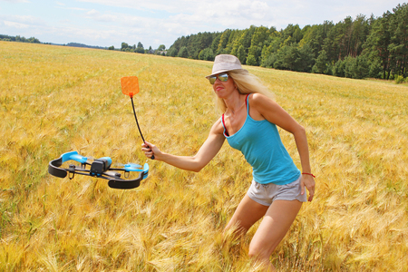 The blonde girl in white hat with a fly swatter drives away drone, against wheat field Stock Photo