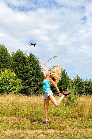 The blonde girl with a fly swatter drives away drone, against blue sky with white clouds Reklamní fotografie