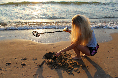 blonde girl in sunglasses with metal detector on the beach