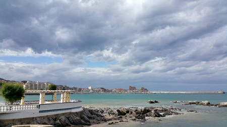 view of the sea shore against the backdrop of the city center on a sunny day. Storm clouds in the sky. Castro-Urdiales, Cantabria, North Spain. Stock Photo