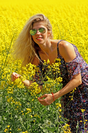 Blonde peasant girl in floral print dress and sunglasses on the yellow blossoming rapeseed field