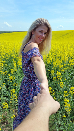 blonde girl in dress with flower print on the blooming yellow rapeseed field