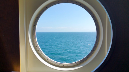 view of the silent sea surface through a porthole of the ship. 版權商用圖片