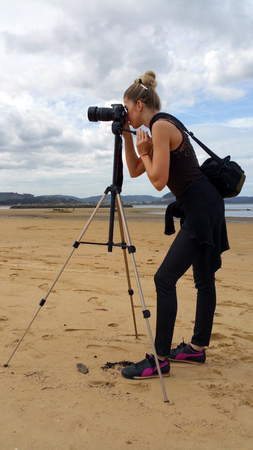 Blonde girl with a camera on a tripod shooting on the beach.