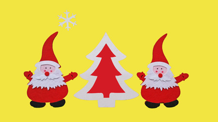 Drawing of Santa Claus and Christmass tree made of glued pieces of felt and plywood on a yellow background, hand-made Imagens
