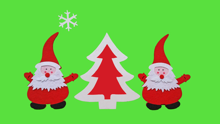 Drawing of Santa Claus and Christmass tree made of glued pieces of felt and plywood on a green background, hand-made