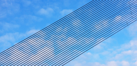 Black metal line rows against a blue sky with white clouds. Background of parallel lines arranged in perspective in an inclined plane. Designer materials. Modern geometric construstion.