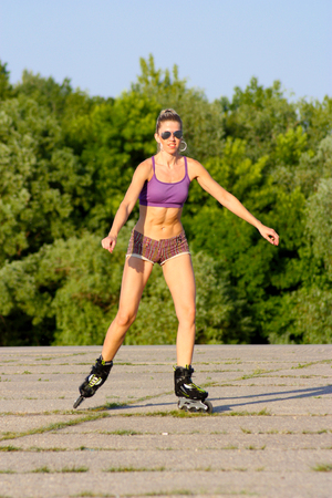 Blond meisje in zonnebril op rolschaatsen bij zonnig weer op een asfaltpad op de achtergrond van de groene bomen Stockfoto