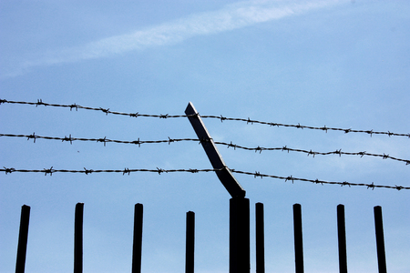 fence with barbed wire against the blue sky. Symbol of freedom of imprisonment.
