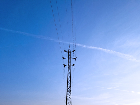 High-voltage lines and cables onthe blue sky background.