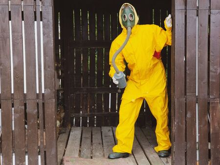 human in a gas mask and protective yellow costume peeping from the doorway 写真素材