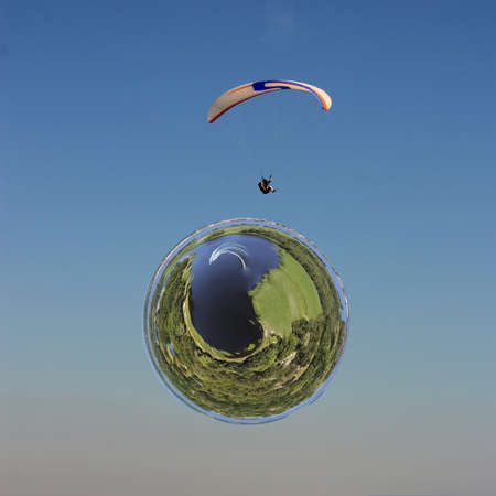 Little planet transformation of spherical panorama 360 degrees. Spherical abstract aerial view on a man is flying on white paraglider in the sky above from a curved space.
