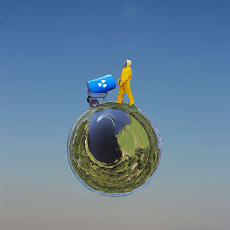 A man in a yellow protective suit and a gas mask is carrying a barrel of toxic waste across planet Earth. Environmental pollution concept. Small planet transformation of a spherical 360 degree panorama. 版權商用圖片