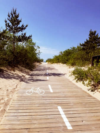 straight wooden pathway on empty to the beach for pedestrians and bicycles in Latvia