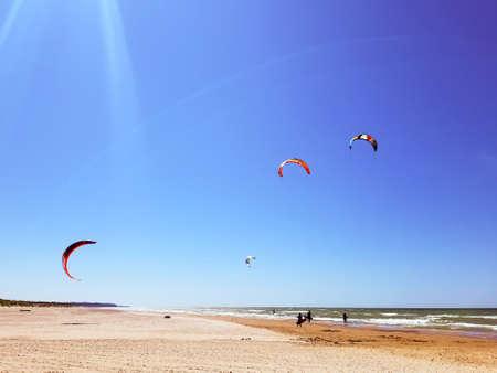 three kitesurf athlete rides the waves of the Baltic Sea. kiteboarding