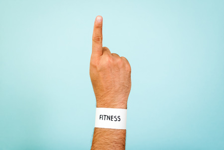 wristband: Paper fitness wristband concept on blue background