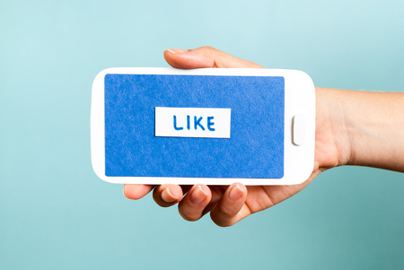 social network icon: Horizontal phone concept showing like button on blue background