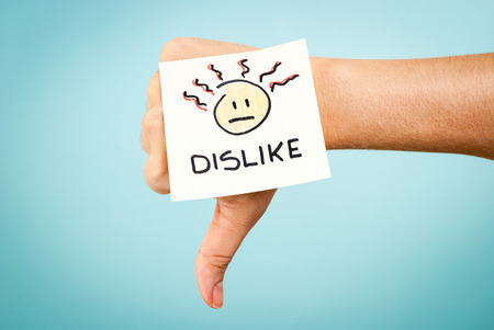 dissatisfaction: Dislike concept with hand on blue background
