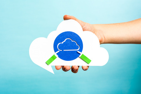 syncing: Hand holding cloud speech bubble with blue cloud. Internet concept.