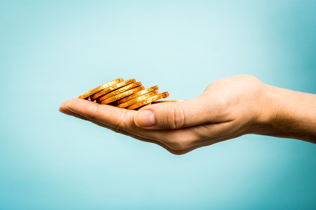 coin bank: Hand holding golden coins concept on blue background. Stock Photo