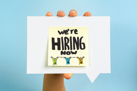we are hiring now note on blue background Archivio Fotografico