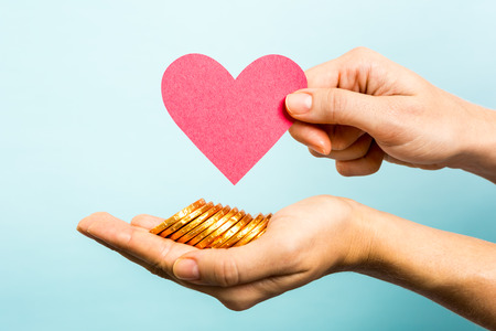 Hand showing red heart paper shape and coins on blue background.  photo