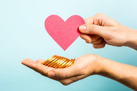 simbolo uomo donna: Mano che mostra la forma di carta cuore rosso e monete su sfondo blu.