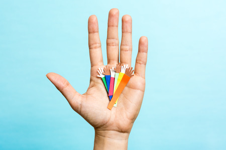 Hand up showing group of diverse multicolor paper hands on blue background.  photo
