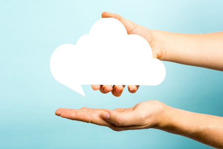 one hand showing a white cloud on blue background.  Stock Photo